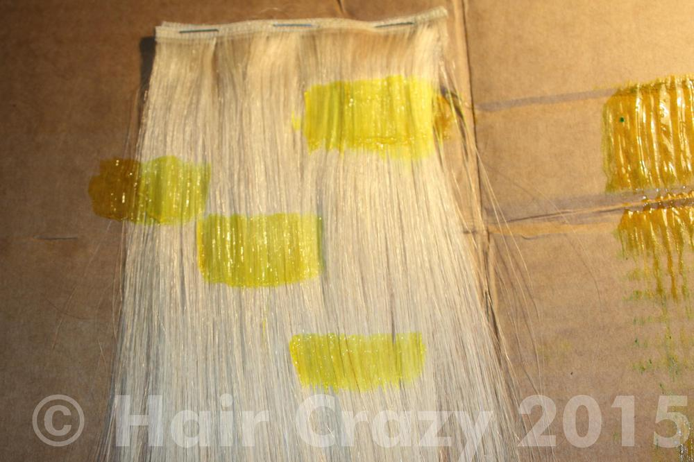 Applying Pravana Locked-In Yellow on a piece of human hair weft.